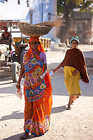 Young Indian woman carrying grain crop in Narlai village in Rajasthan, Northern India
