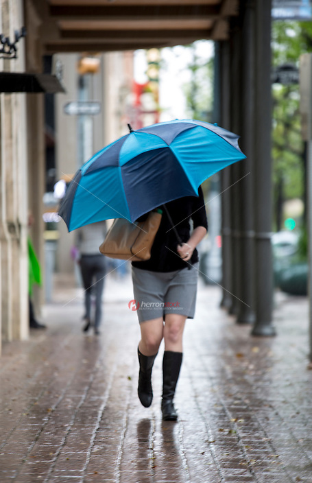Woman holding umbrella walks down a wet rainy sidewalk on Congress Avenue in downtown Austin, Texas on a gray stormy day - Stock Image.