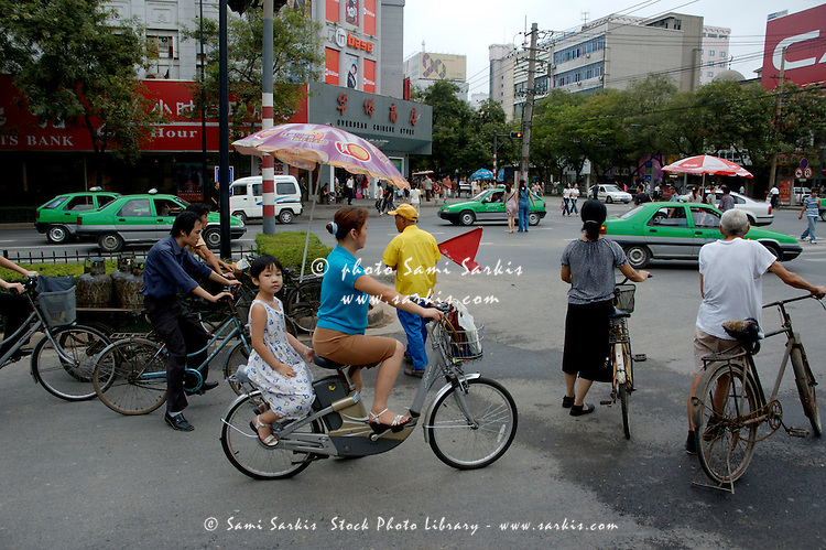 People riding bicycles and  merge together with cars on a busy street in Xi'an, Shaanxi, China.