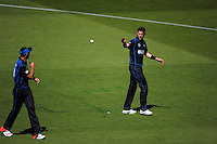 Tim Southee passes the ball to Adam Milne during the ICC Cricket World Cup one day pool match between the New Zealand Black Caps and England at Wellington Regional Stadium, Wellington, New Zealand on Friday, 20 February 2015. Photo: Dave Lintott / lintottphoto.co.nz