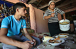 Roma families in Barbulesti, Romania. Laura Duduveica and her family share a house in Barbulesti together with 3 other families since they have been deported from France. Laura and her son Romeo are having lunch together. Romeo has been deported from France where he was a student.