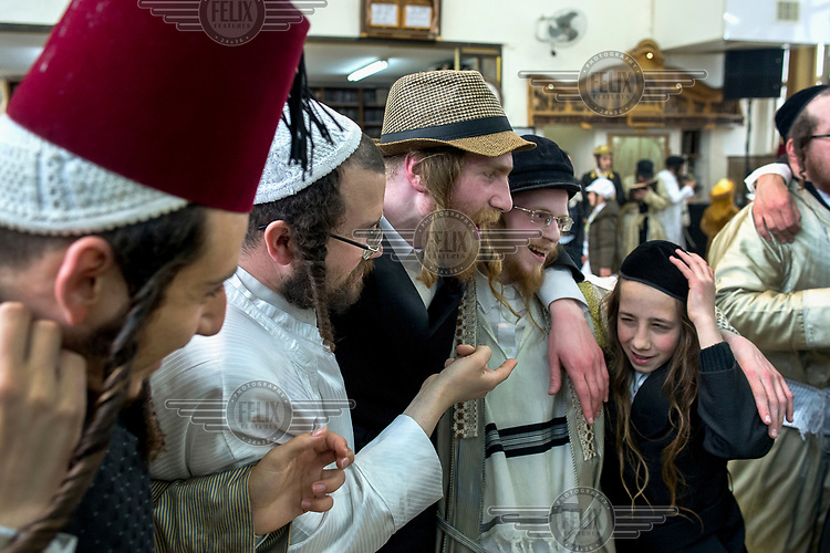 A group of men dance in-line during a feast celebrating the holiday of Purim held in the ultra-orthodox Jewish neighbourhood of Me'a She'arim.