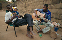 Mali. Bamako. A young man plays the guitar to a friend and his youngest brother in the home courtyard. © 1997 Didier Ruef