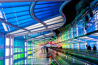 Travelers on moving sidewalk in tunnel at United terminal passing Sky's the Limit (neon sculpture by artist Michael Hayden) at O'Hare International Airport, Chicago, Illinois USA.