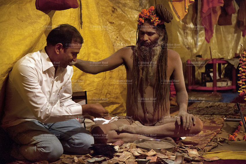India. Uttar Pradesh state. Allahabad. Maha Kumbh Mela. An Indian Hindu devotee wearing werstern clothes gives money to a Naga (naked) Sadhu after atending spiritual discourses. The Naga Sadhu sits on a carpet inside his tent in Sangam. The Kumbh Mela, believed to be the largest religious gathering is held every 12 years on the banks of the 'Sangam'- the confluence of the holy rivers Ganga, Yamuna and the mythical Saraswati. In Hinduism, Sadhu (good; good man, holy man) denotes an ascetic, wandering monk. Sadhus are sanyasi, or renunciates, who have left behind all material attachments. They are renouncers who have chosen to live a life apart from or on the edges of society in order to focus on their own spiritual practice. The significance of nakedness is that they will not have any worldly ties to material belongings, even something as simple as clothes. A Sadhu is usually referred to as Baba by common people. The Maha (great) Kumbh Mela, which comes after 12 Purna Kumbh Mela, or 144 years, is always held at Allahabad. Uttar Pradesh (abbreviated U.P.) is a state located in northern India. 7.02.13 © 2013 Didier Ruef