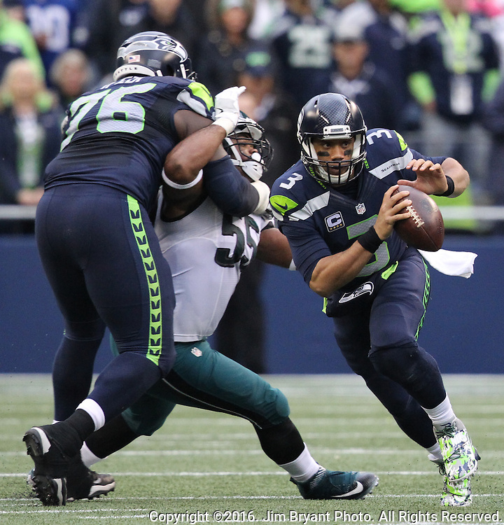 Seattle Seahawks quarterback Russell Wilson (3) scrambles against Philadelphia Eagles defensive tackle Fletcher Cox (91)at CenturyLink Field in Seattle, Washington on November 20, 2016.  Seahawks beat the Eagles 26-15.  ©2016. Jim Bryant Photo. All Rights Reserved.