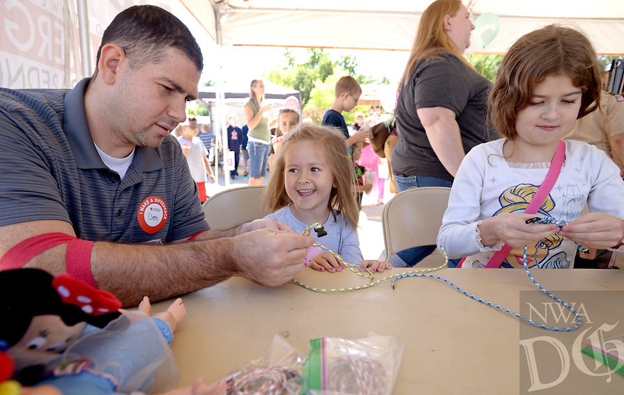 NWA Democrat-Gazette/BEN GOFF @NWABENGOFF<br /> Donald Hicks (from left) helps his daughters Katie Hicks, 5, and Payton Hicks, 9, of Centerton, braid their own paracord survival bracelets on Saturday Sept. 12, 2015 during the Northwest Arkansas Emergency Preparedness Fair at the Church of Jesus Christ of Latter-Day Saints in Bentonville. The event included a variety of informational booths, a blood drive, games for children, appearances by emergency vehicles and meteorology classes to help families be prepared for emergencies.