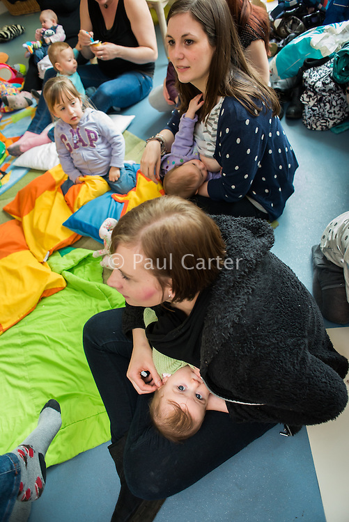 "Two mothers breastfeeding their babies at a drop-in breastfeeding support centre.<br /> <br /> Image from the ""We Do It In Public"" documentary photography project collection: <br />  www.breastfeedinginpublic.co.uk<br /> <br /> Dorset, England, UK<br /> 17/04/2013"