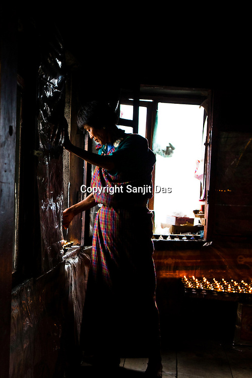 A Bhutanese woman lights butter lamps inside a temple next to the Taktsang Temple, also popularly known as The Tiger's Nest temple in Paro, Bhutan.