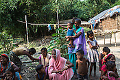 21 year old Seema Devi (centre) sits with other family members and neighbours outside their hut in Shivpur Hariyya village in Raxaul district of Bihar.