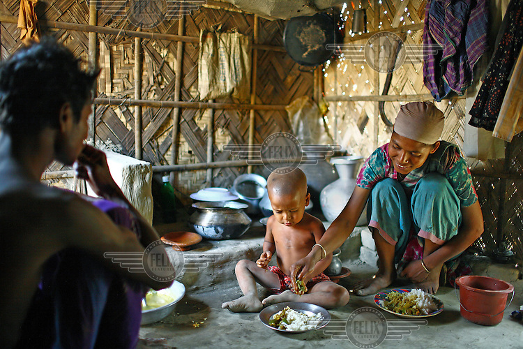 The family of a labourers, who work in a brick making factory, eat a meal together at their home in Gazipur..