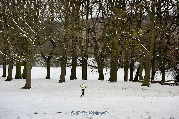 A jogger runs on Hampstead Heath in the snow, London.