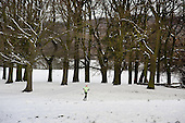 A jogger runs on Hampstead Heath in the snow, London.