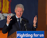 Former President Bill Clinton, raising his hands while giving a speech, is the headline speaker as he campaigns at an Organizing Event rally in Elmont, Long Island, on behalf of his wife, Hillary Clinton, the leading Democratic presidential candidate, and former Secretary of State and U.S. Senator for New York. Podium has 'Fighting for us' slogan on sign. The New York Democratic Primary takes place April 19th.