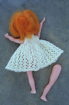 Girl doll with white knitted dress and ginger hair lying face down on grey slate with one of her legs separated from her body