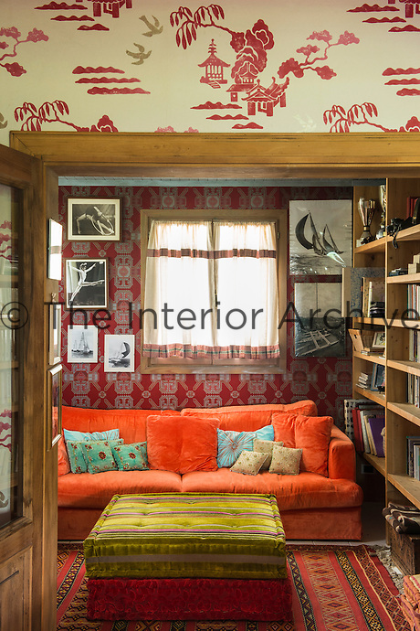 The library is a small room which connects to the main living/dining area and is dominated by a bright orange sofa