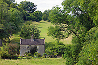 Cottage in the landscape at Temple Guiting in The Cotswolds, Oxfordshire, UK