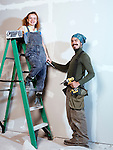 Portrait of a smiling young couple renovating, patching up drywall