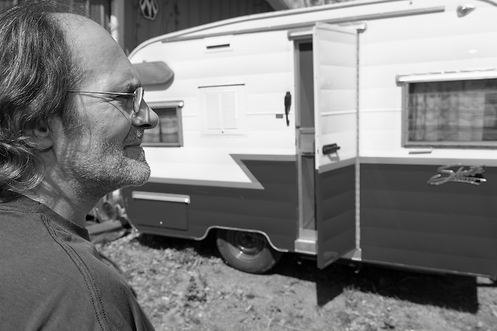 Man with glasses and scruffy beard standing next to an old Shasta trailer