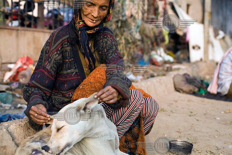 """70 year old Kathleen Lama, a homeless woman, fusses over a stray dog. Originally from Darjeeling she has now made her home on a patch of land in Nizamuddin, Delhi.""""I came to Delhi with my husband in 1965. We lived for some time in Old Delhi and then we had bad luck and became homeless. I don't want to leave here because my husband died in this place and anyway, I serve all the animals here now."""""""