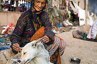 "70 year old Kathleen Lama, a homeless woman, fusses over a stray dog. Originally from Darjeeling she has now made her home on a patch of land in Nizamuddin, Delhi.""I came to Delhi with my husband in 1965. We lived for some time in Old Delhi and then we had bad luck and became homeless. I don't want to leave here because my husband died in this place and anyway, I serve all the animals here now."""