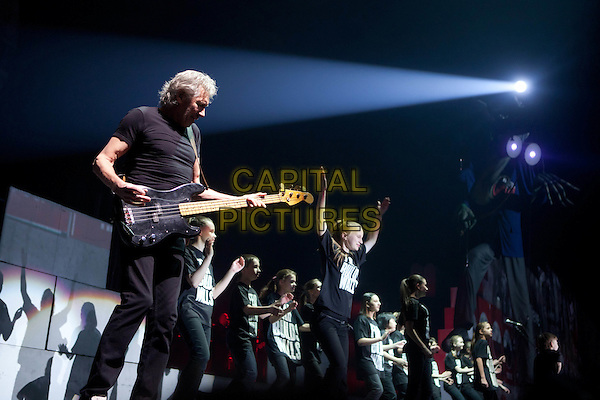 Roger Waters.Roger Waters concert in Moscow, Russia.April 23rd, 2011.stage concert live gig performance performing music in on half length black t-shirt guitar bass jeans denim profile backup dancers .CAP/PER/SB.©SB/PersonaStars/CapitalPictures