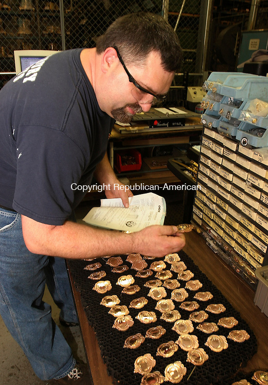 CHESHIRE, CT-28 June 2005-062805TK06  Ken Mitrik of Thomaston inspects the detail of security badges manufacture for police, fire and military requirements.  om Kabelka staff photo (Ken Mitrik, security badges)CQ