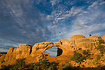 Blue sky and white clouds over Broken Arch in Arches National Park near Moab, Utah, USA at sunrise.