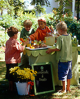 A group of young boys having a lemonade party under the trees