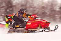 SNOWMOBILERS COMPETE IN A HILL CLIMB RACING EVENT AT MARQUETTE MOUNTAIN SKI HILL IN MARQUETTE MICHIGAN.