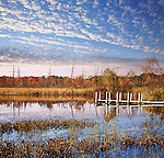 A Small Boat And Fishing Pier Under Beautiful Morning Skies On Lake Sixteen During Autumn, Oakland County Michigan. USA