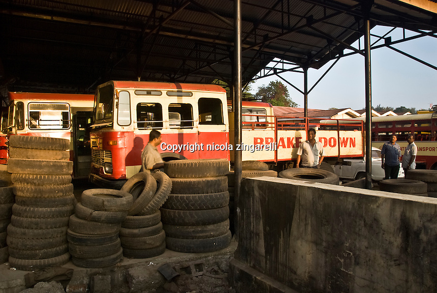 Chatham bay, andaman islands, India. The local deposit for the most common vehicles of road transportations around the island. Trucks, buses and lorries with many discarded tyres