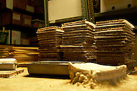 Stacks of Lacewing Larvae Units stand behind the glue board in the assembly room at Rincon Vitova Insectaries in Ventura, Calif., on Wednesday, October 17, 2008.  The glue glob on the board has grown layer by layer as a paint roller is used to glue the organdy covers on.  Kyra Ankenbruck encountered the glue board in May 2006.  ?It wasn?t much smaller than now,? Ankenbruck comments. (Photo by Bryce Yukio Adolphson, © 2008)