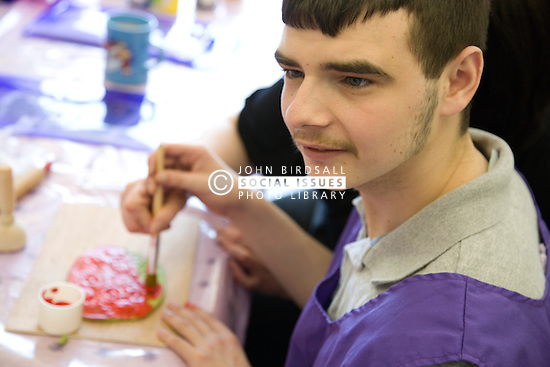 Day Service User with learning disability painting modeling clay shape,