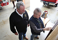 NWA Democrat-Gazette/DAVID GOTTSCHALK Peter Reagan (left) and Dennis Mullens, both charter members of the Fayetteville Fire Fighters Association Local No. 2866, look over the original charter before the ringing of a ceremonial bell Wednesday, February 28, 2018, at Station 1 marking the 100th anniversary of the birth of the International Association of Fire Fighters. The Fayetteville Fire Department had 35 original members in their local charter that began on January, 25, 1982. The International Association of Fire Fighters was started in Washington D.C. in 1918.