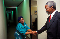 Nelson Mandela greeting a staff member at his office shortly after he became President.