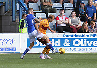 Kevin Holt gets a foot to the ball before Christian Ilić in the SPFL Betfred League Cup group match between Queen of the South and Motherwell at Palmerston Park, Dumfries on 13.7.19.