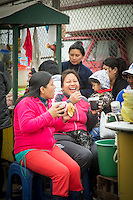 Women outside fish market. Drinking Peruvian drink Chicha, Lima, Peru, South America