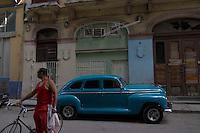 street scene in Havana, Cuba, man in red shirt standing in front of blue oldtimer car