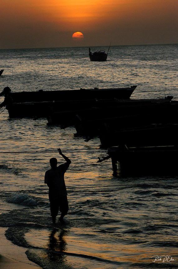 A Zanzibar resident tends to fishing boats as the tide rises in the beach adjacent to Stone Town, Zanzibar. (Rick D'Elia)