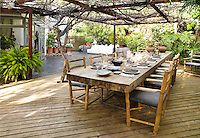 An oak table laid for lunch is set out on a raised decked terrace shaded by a vine covered iron pergola.