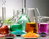 LABGLASS CONTAINING TRANSITION METAL COMPOUNDS<br /> Solids & Solutions in Mortar, Flasks & Watchglass<br /> Pale green Nickel Chloride in mortar & flask; blue-green Nickel Sulfate in flask & watchglass; crimson Cobalt Chloride in watchglass & flask; orange Sodium Dichromate in watchglass & flask; purple Potassium Permanganate in beaker & watchglass.
