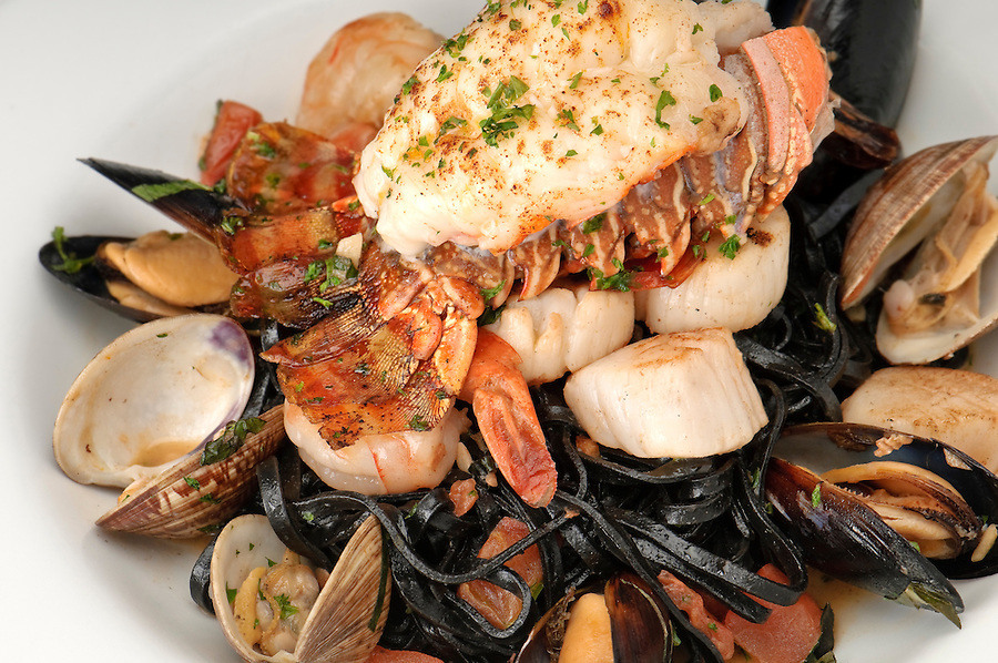 Plate of lobster served with sauteed jumbo shrimp, oysters and linguini pasta.
