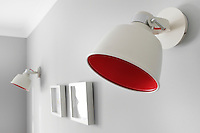 A pair of red and white wall lights in a grey room