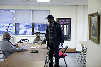 Mr Sinclaire Waithe  ( on right ) and Mr Timothy McBride ( Center ) who both attend the HICAP classes, leave a table game in the main recreation center of   the Gen Chauncey M. Hooper Towers, that hosts the Harlem Internet Computer Access program taught by instructor Merle Bush in Harlem, Manhattan, NY, USA on November 15, 2011.