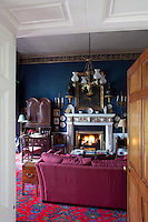 A marble fireplace is the focal point of this living room with walls painted a royal blue