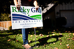 A campagin volunteer for Republican congressional candidate Ricky Gill plants a campaign sign in a supporter's front yard in Stockton, Calif., September 18, 2012.