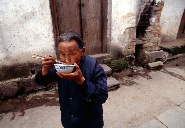 A woman eating rice from a bowl on a rural village street in Dachang, China, Lesser Three Gorges, along Daning River