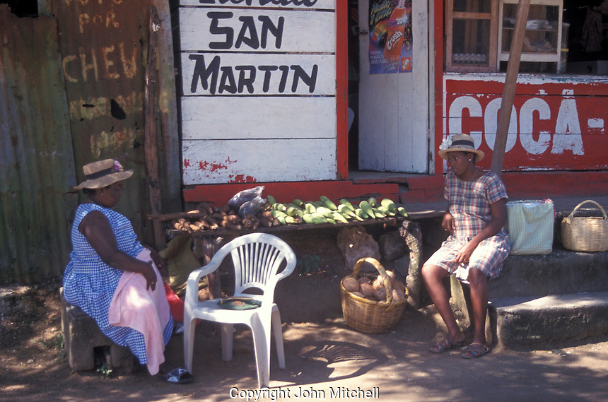 Two black women chatting infront of a store in the town of Livingston on the Caribbean coast of Guatemala