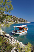 Turkey, Province Antalya, island Kekova, near Demre: Small Gulet boat in craggy cove | Tuerkei, Provinz Antalya, unbewohnte Insel Kekova bei Demre: Ausflugschiff (Gulet ) vor Anker